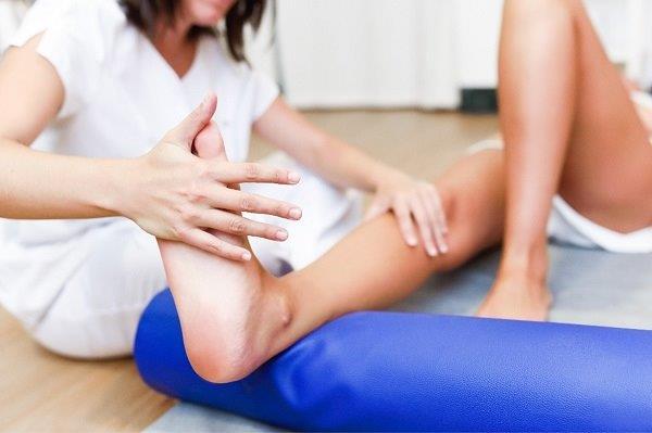 fizioterapeut pregleda pacijentu koleno na podu